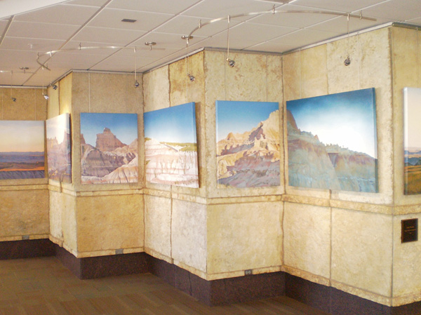 Stretched canvas prints suspended on stone walls at Rapid City Regional Airport (RAP) using Classic System by AS Hanging Systems.