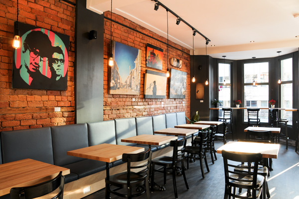 Art wall display on café brick wall using Click Rail System by AS Hanging Systems