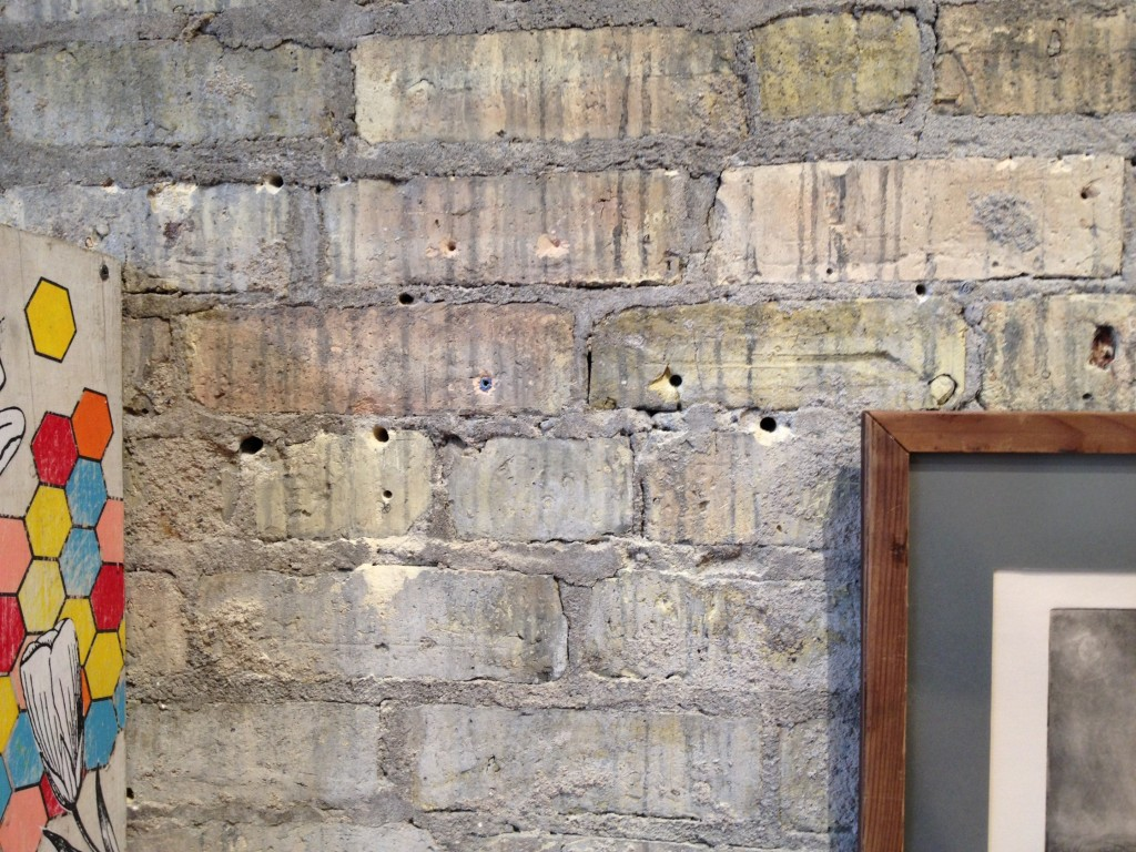 Brick wall showing excessive art display damage.
