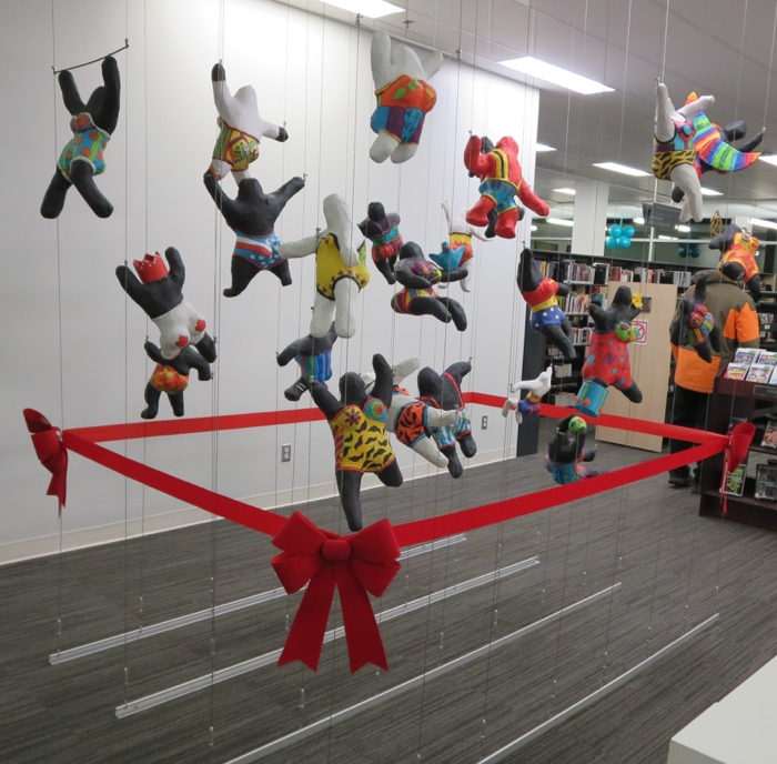 3D art display created using a tensioned cable system in multi-purpose room of public library.