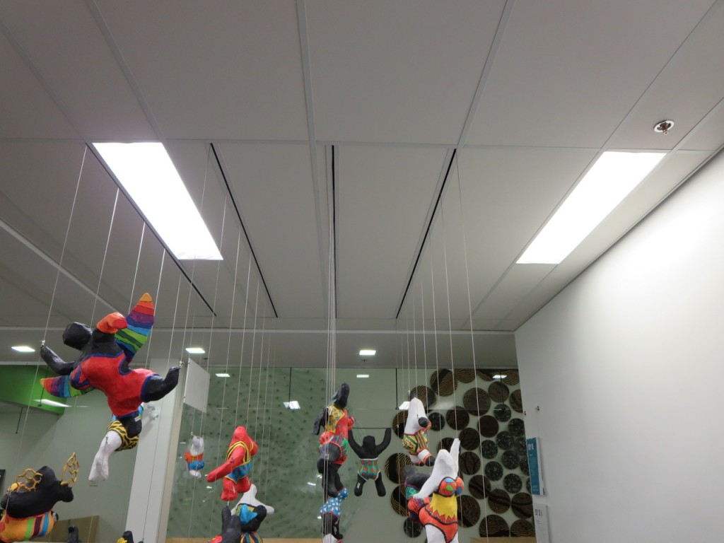 Floating 3D art display using a Tensioned Cable System with cable passing through slots fabricated into ceiling tiles.