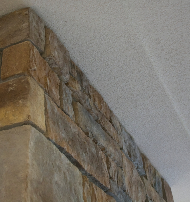 Stone fireplace with irregular front surface.