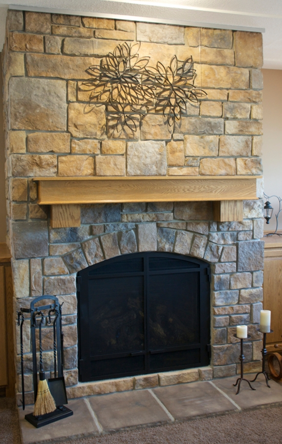 Stone fireplace with irregular surfaces using Ceiling Track as an art hanging system.